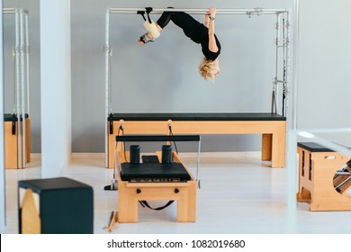 Female pilates instructor in black sportswear working out in cadillac reformer in modern eco interior of pilates studio.