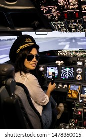 Female Pilot in the Airplane Cockpit. Pilot wearing sun glasses and hat
