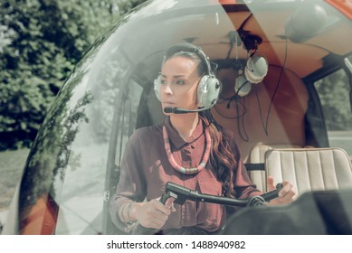 Female pilot. Famous professional female pilot holding control wheel sitting in little private helicopter