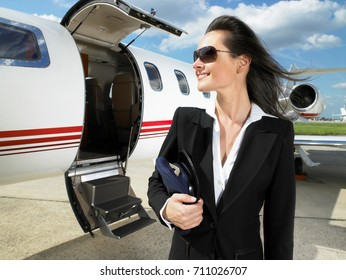 Female pilot in front of private jet.