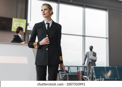 female pilot with suitcase at airport reception