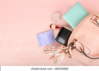 Female pink bag and accessories on a pink background.