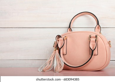 Female pink bag on a desk on a wooden background.