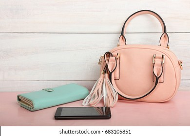 Female pink bag on a desk on a wooden background.