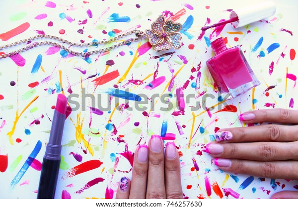 Female pink set with  necklace chain in shape of flower, pink nail polish and lipstick. Hands with pink manicure on brush strokes background