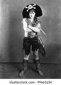 Female in a  pirate's costume standing with her arms crossed and holding a knife