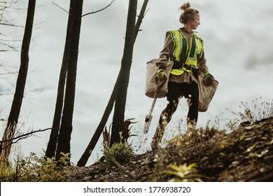 Plantando árboles en el bosque. Mujer plantadora de árboles con chaleco reflexivo caminando en el bosque cargando una bolsa llena de árboles y una pala.