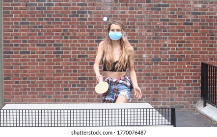 female playing ping pong outside by a brick wall