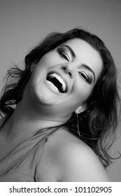 Female Plus size model posing in the studio, bw face portrait, on grey background. The woman is smiling in a happy manner. Good for concept of health, happiness, dieting, obesity, weight loss.