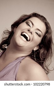 Female Plus size model posing in the studio, duotone face portrait, on grey background. The woman is smiling in a happy manner. Good for concept of health, happiness, dieting, obesity, weight loss.