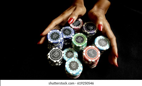 The female poker player with paint red nails, pushing her poker chips going all in forward to bet on black fabric,  gambling and casino business concept