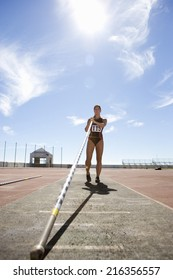 Female pole vault athlete with pole, low angle view