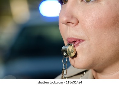 a female police officer about to blow into her whistle as she directs traffic.