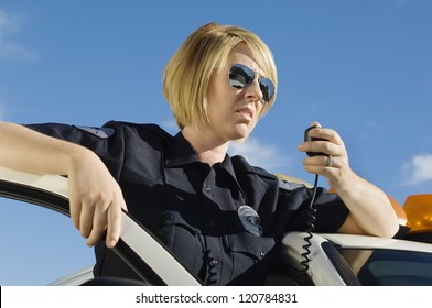 Female police officer communicating on walkie-talkie standing by car