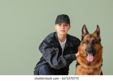 Female police officer with dog on color background