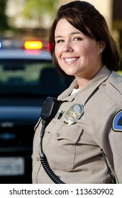 a female police officer smiles while standing in front of her patrol car.