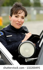 a female police officer standing next to her car as she writes a ticket.