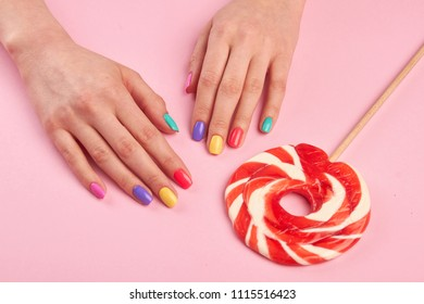 Female polished nails and lollipop. Woman hands with varnished nails and big lollypop on colored table, top view. Candy colored nails.