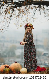 Female portrait. Charming pregnant woman in long dress and red scarf stands before a bunch of pumpkins outside