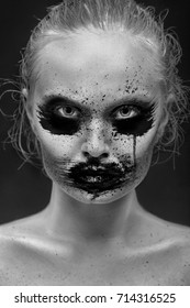 female portrait with creative smeared makeup on black background, monochrome image