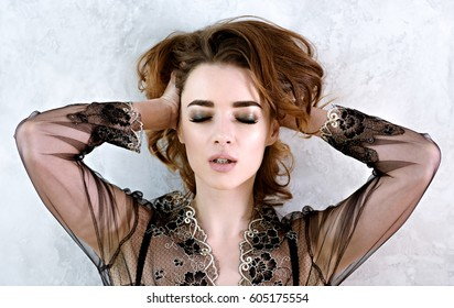 Female portrait of cute lady in black robe indoors. Close up beautiful sexy model girl in elegant pose. Closeup beauty brunette woman with hairstyle