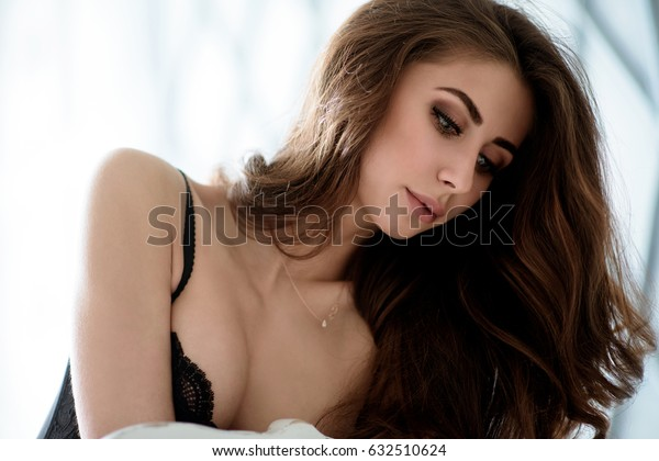 Female portrait of cute lady in black bra indoors. Close up beautiful sexy model girl in elegant pose. Closeup beauty brunette woman with hairstyle