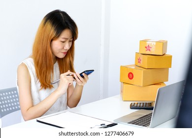 Female portrait happy face with hand holding mobile phone close up, Online marketing shopping business concept, Blurred laptop, parcel brown box, on white table desk background with copy space.
