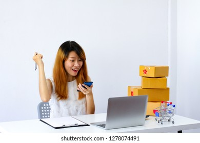 Female portrait happy face with hand holding mobile phone, Online marketing shopping business successful concept, Blurred laptop, parcel brown box, on white table desk background with copy space.