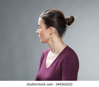 female portrait - thinking 30s woman with tied brown hair looking back for questions and nostalgia on her past,profile view,studio shot