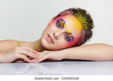 Female portrait with unusual face art make-up. Paint on brows, hair, around eyes and with paint drips on the neck. Woman sitting at a white table and wearing a salad-colored tank top T-shirt.