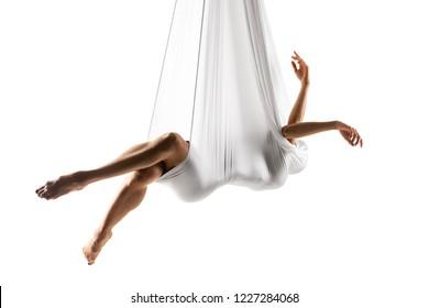 female posing aerial anti-gravity yoga on a hammock