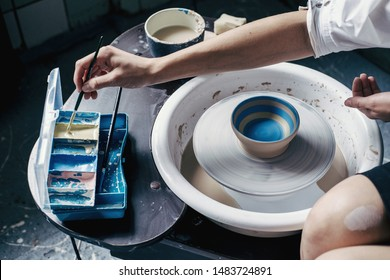 Female potter hands working with clay in workshop. White desk on background