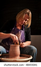 Female potter at wheel in studio shaping clay