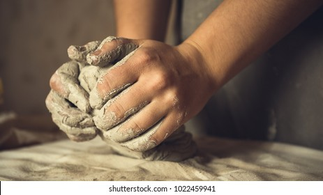 Female potter works with clay, craftsman hands close up, kneads and moistens the clay before work, toned