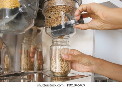 Female Pours Green Lentils from Vending Machine in a Glass Jar. Young Vegan Woman Shopping at Zero Waste Shop. No plastic Conscious Minimalism Lifestyle Concept.