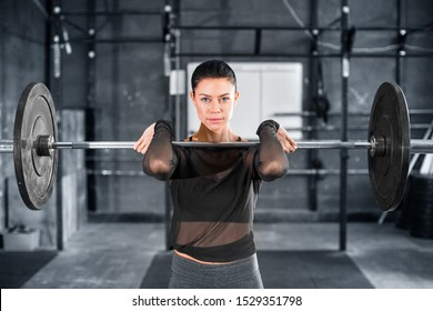 Female powerlifter doing a clean and jerk with heavy weights. Close up portrait.