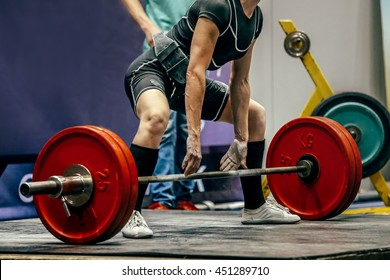 female powerlifter preparing for deadlift of barbell during competition of powerlifting