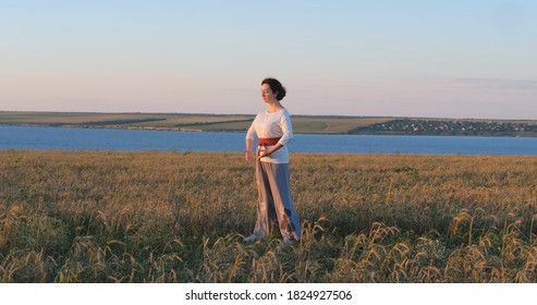 Female practicing qigong in summer fields with beautiful sunset on background