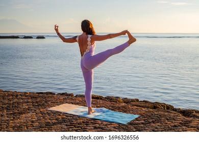 Female practicing Utthita Hasta Padangusthasana, Extended Hand-To-Big-Toe pose. Hand in gyan mudra. Balancing asana. Perfect body shape. Healthy lifestyle. View from back. Yoga retreat. Bali Indonesia