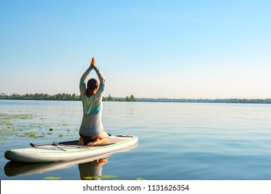 Female practicing yoga on a SUP board during sunny morning on a large river. Stand up paddle boarding - awesome active recreation in nature. Back view.