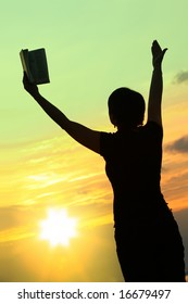 female praying with bible against summer sunset