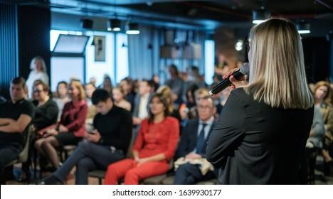 Female presenter speaks to audiences at seminar