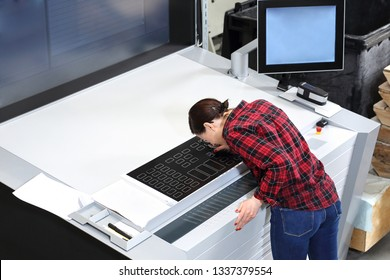 A female printer at the stage watching the print quality through a magnifying glass.