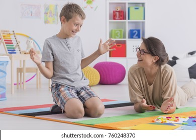 Female private tutor working with little boy teaching child to read using colorful letters