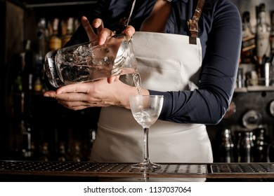 Female professional barman pouring fresh summer drink into an elegant cocktail glass on the dark bar counter