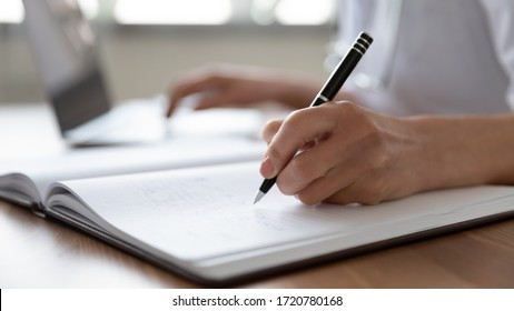 Female professional doctor hand making notes in medical journal using laptop computer sitting at desk. Woman physician, nurse or pharmacist wearing white coat writing in paper notebook. Close up view - Shutterstock ID 1720780168