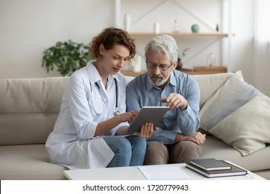 Female professional doctor showing medical test result explaining prescription using digital tablet app visiting senior man patient at home sitting on sofa. Elderly people healthcare tech concept.