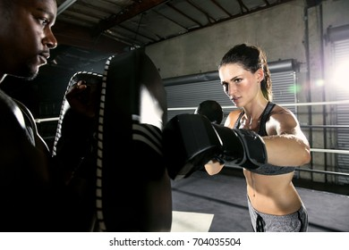 Female professional fighter with trainer instructor practicing at gym in boxing ring
