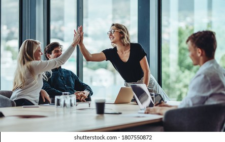 Female professional giving a high five to her colleague in conference room. Group of colleagues celebrating success in a meeting.