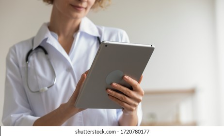Female professional medic doctor holding modern pad using digital tablet remote telemedicine app in hospital working online. Healthcare technology telehealth ehealth concept. Close up view, copy space